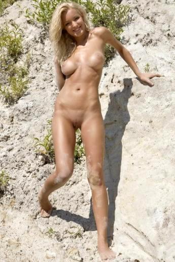 Мокрая красотка голышом в песчаном карьере тискает аппетитные дойки