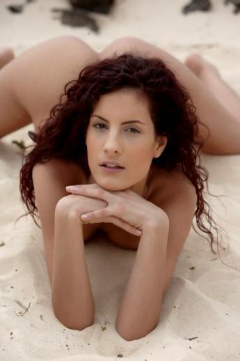 Длинноногая пляжная модель распускает рыжие кудри поддразнивая маленькой попкой