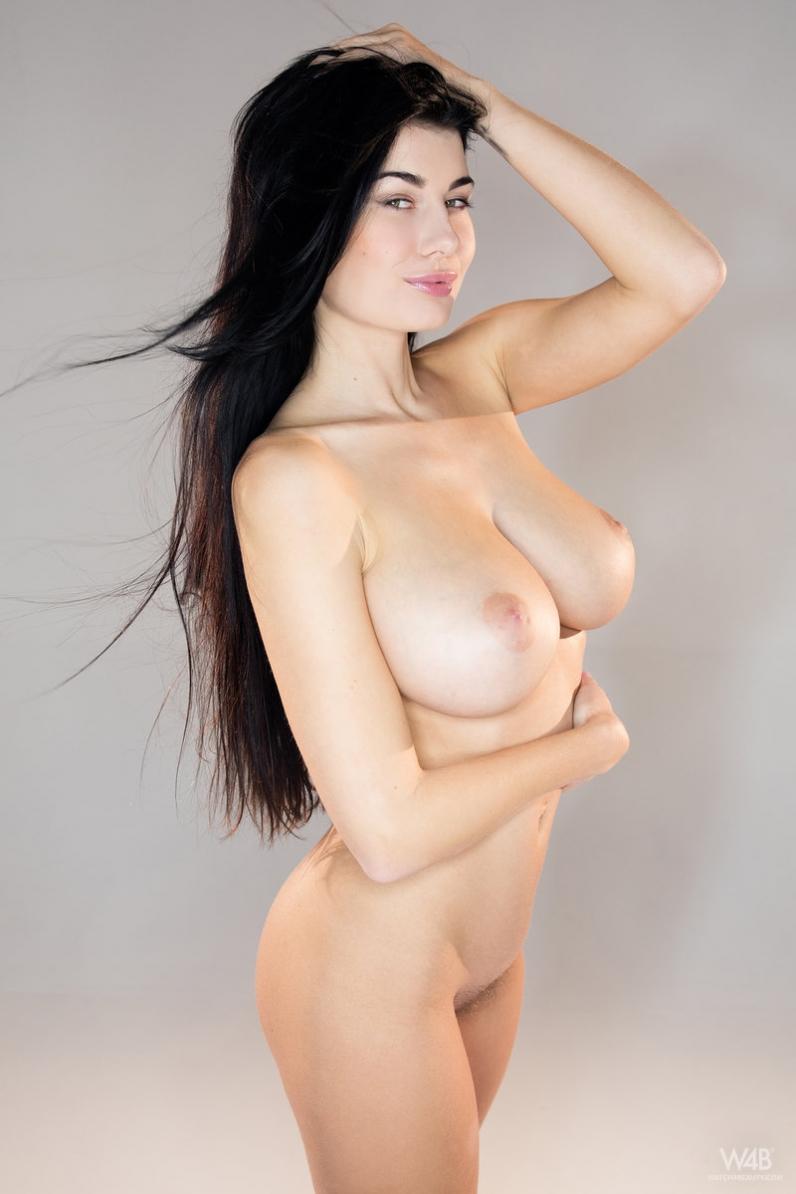 Знойная голая брюнетка с красивым лицом и длинными волосами ...