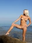 Белокурая модель снимает на пляже трусы и голышом забегает в море разбрызгивая бирюзовую воду на маленькую грудь и классную попу, фото 12