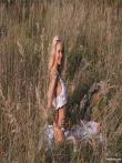 Веселая девушка посреди поля снимает трусы с приятной письки, фото 1