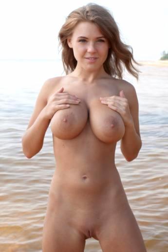 Приятная девушка с голым телом и крупными сиськами в море (18 фото)