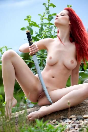 На природе рыжая модель Ариэль с оголенным самурайским мечом