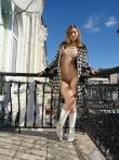 Худая бабенка на балконе позирует в верхней одежде без трусов красуясь в кожаных сапогах маленькой жопой, фото 4