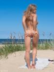 Длинноволосая блондинка в солнцезащитных очках красуется голой попкой и большими сиськами на солнечном пляже, фото 8