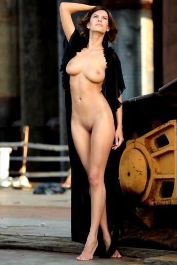Модель с длинными ногами распахивает пеньюар с крупными голыми сиськами позирует на стройке