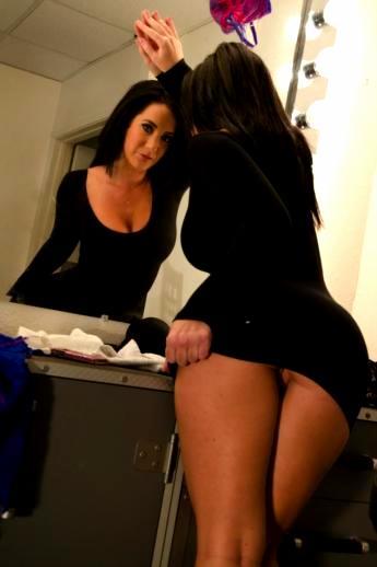 Жопастая зрелая порнозвезда у зеркала в коротком обтягивающим зад платье без трусов