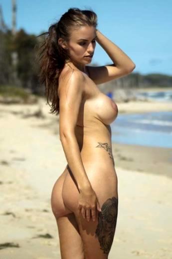 На пляже красивая девушка с татуировками оголяет аппетитные сиськи и смачную жопу под ласковым солнцем