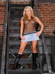 Длинноногая блондинка на лестнице стягивает джинсовую юбку с большой голой жопы, фото 1
