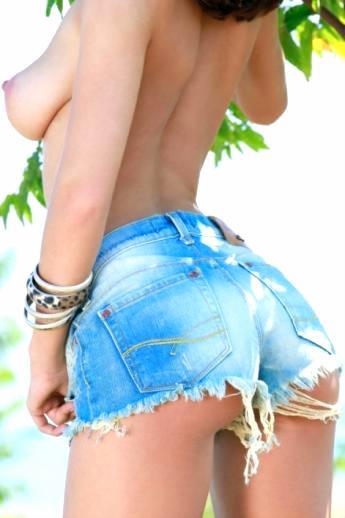 Красивая попа в раваных джинсовых шортах большегрудой брюнетки в саду