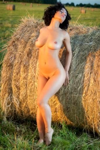 Стройная показывает красивые сиськи на природе в поле