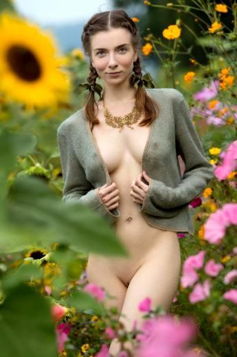 Девушка с косичками на природе обнажает стройное тело с упругими титьками и маленькой жопой