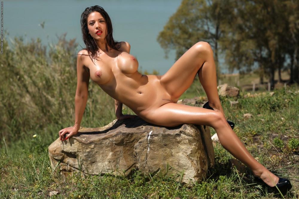 На природе красивая голая брюнетка Savannah обмазывает горячее тело маслом