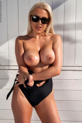 Большие дойки в разрезе черного купальника блондинки в солнцезащитных очках