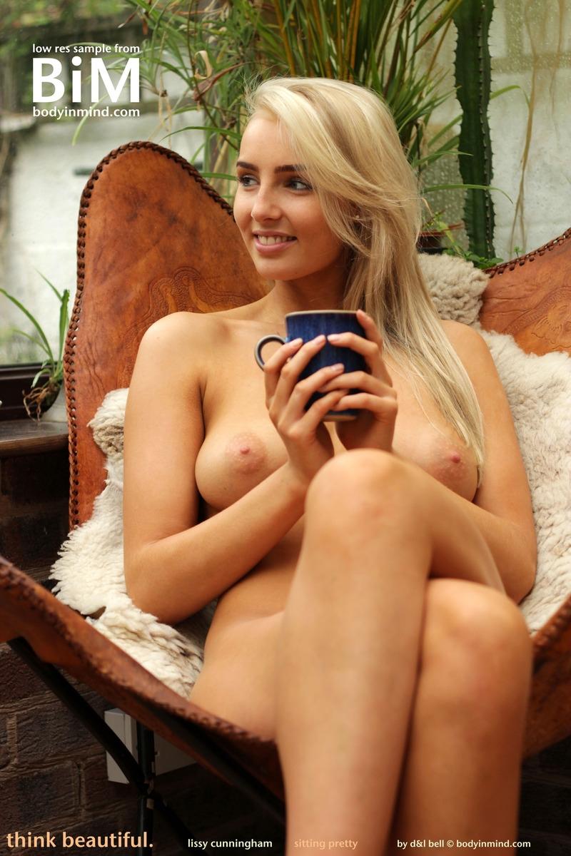 Изысканная блондинка с красивой фигурой и большой голой грудью позирует без трусов